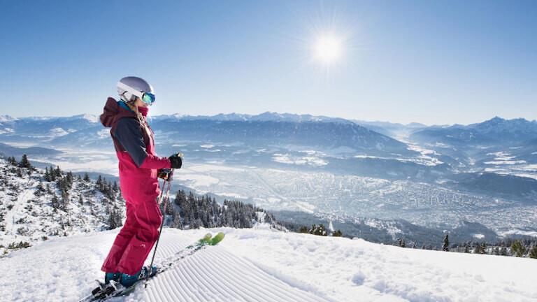 Esquiadora observando las vistas de Innsbruck desde lo alto de una montaña.