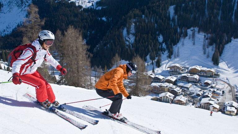 Dos personas esquiando en Salzburg-Sportwelt con el pueblo a sus pies.