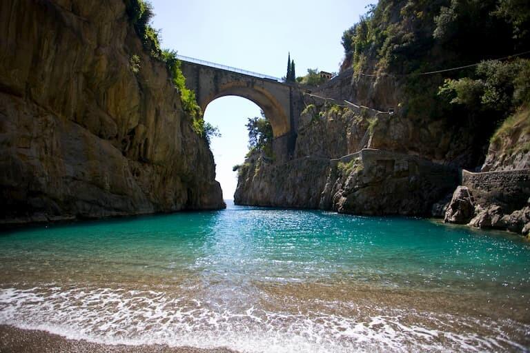 Playa Marina di Furore con un curioso puente entre acantilados que hace de puerta al mar.