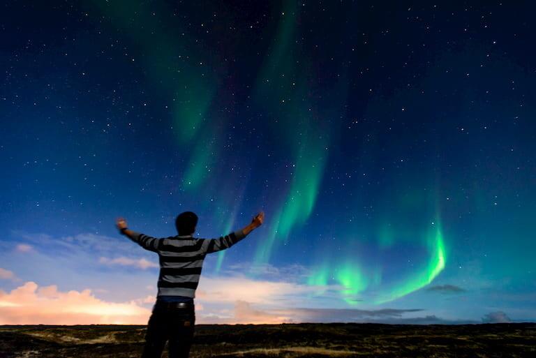 Hombre viendo Auroras Boreales en Islandia