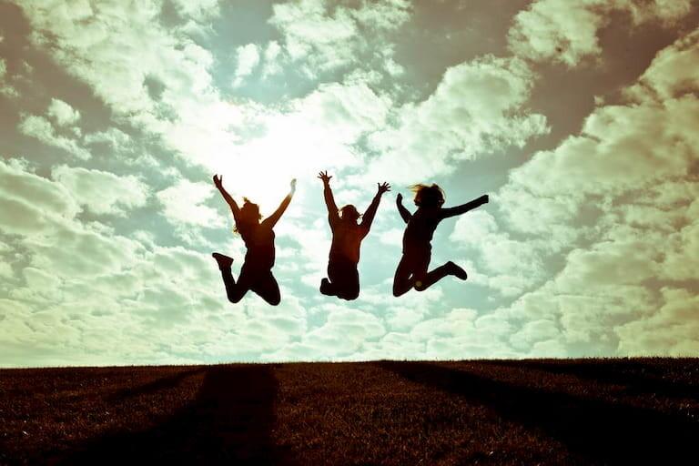 Silueta de 3 amigas saltando de alegría