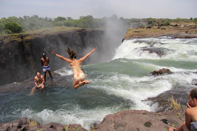 Personas bañándose en la piscina del Diablo, al borde de las cataratas Victoria