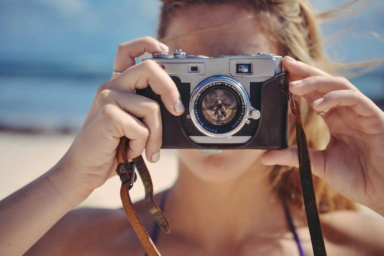 Chica haciendo una foto con una cámara analógica.