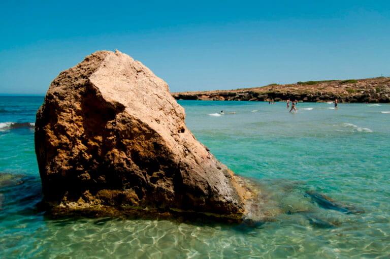 Una roca en medio de las aguas de la Playa Calamosche