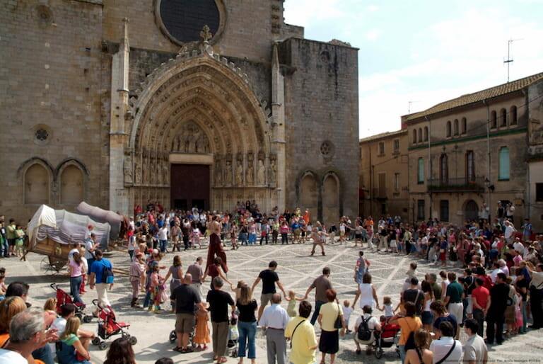 Fiesta mayor con gente bailando delante de la iglesia de Castelló d'Empúries