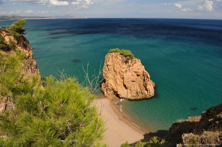 Una gran roca rojiza en medio de la playa de la Illa Roja, en Begur