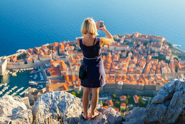 Una chica hace una foto con el móvil de las vistas de Dubrovnik desde una montaña