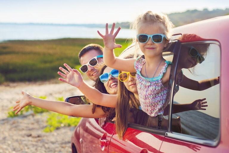 Familia saludando desde la ventana de un coche