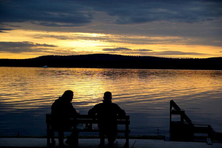 2 hombres sentados en un banco observando el Sol de Medianoche