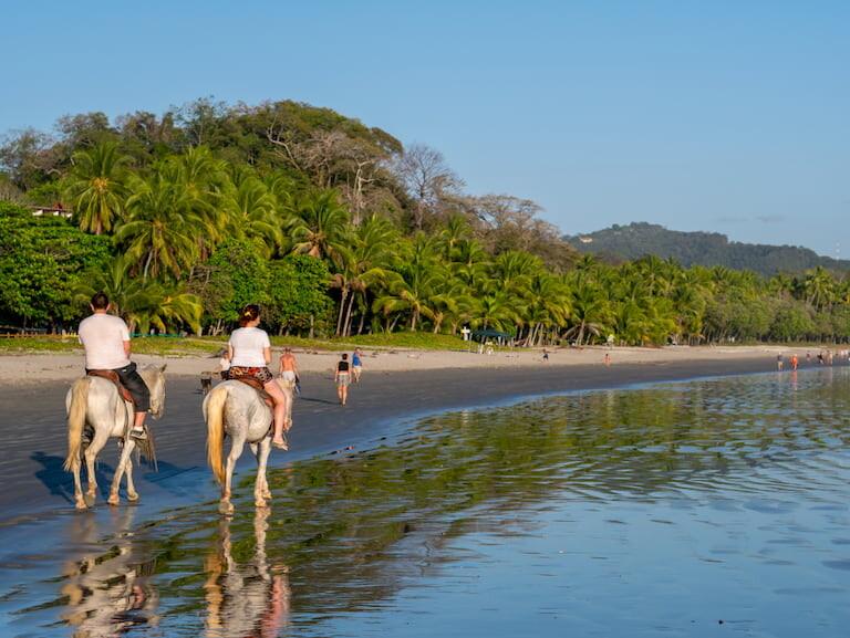 Gente montando a caballo por una playa de Costa Rica