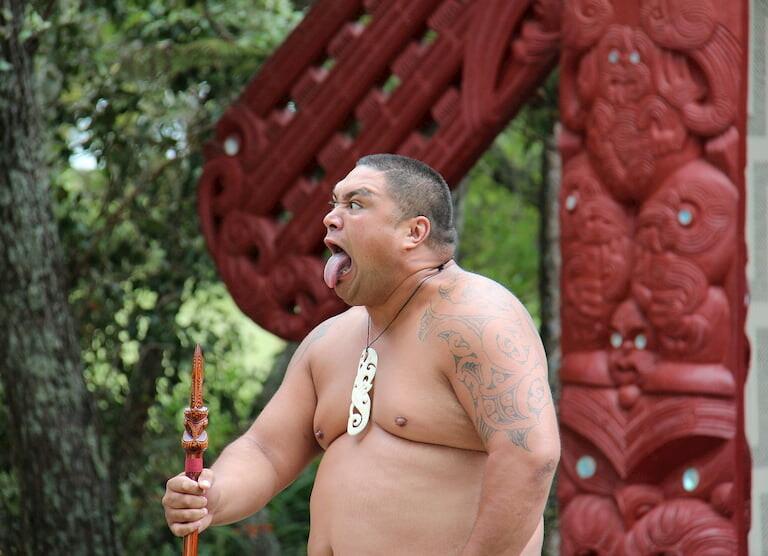 Hombre maorí tatuado saca la lengua en gesto amenazante