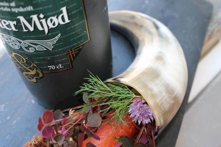 Cerveza y cuerno vikingo con flores y hierbas dentro