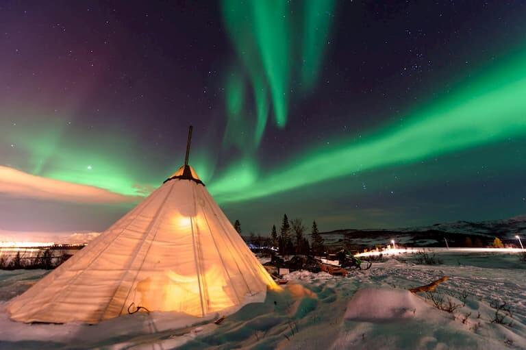 Auroras en Noruega frente a un campamento nevado