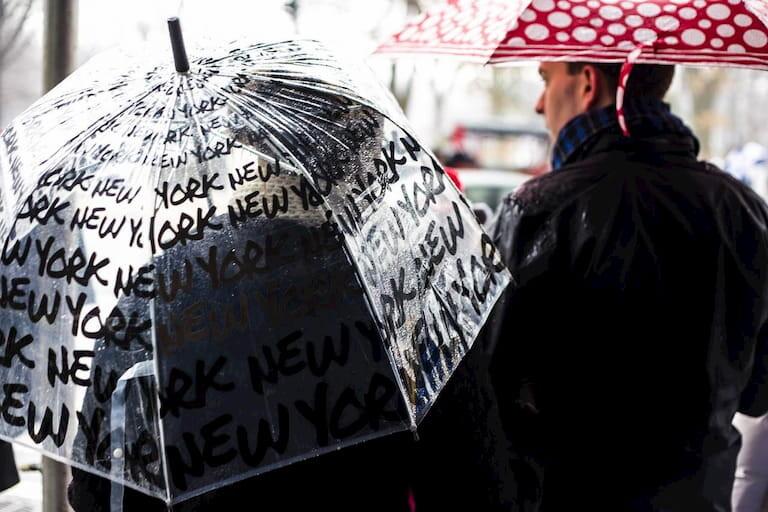 Gente tapándose con paraguas mientras llueve