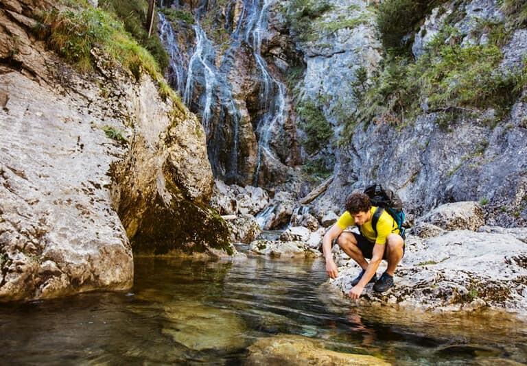 Chico en una cascada de los Alpes