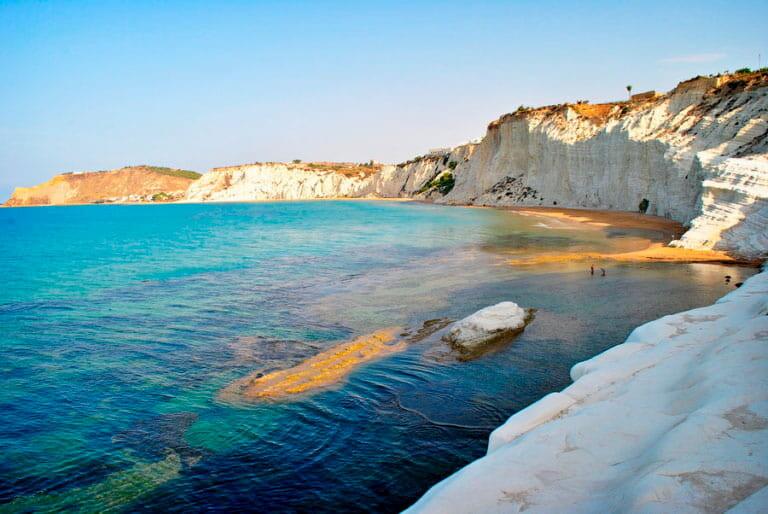 Una playa rodeada de paredes de roca blanca.