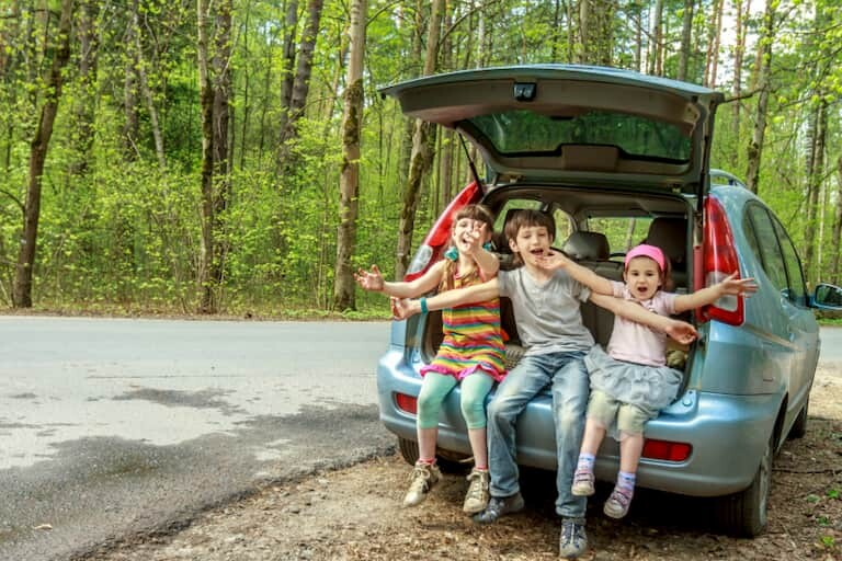 3 niños sentados en el maletero de un coche