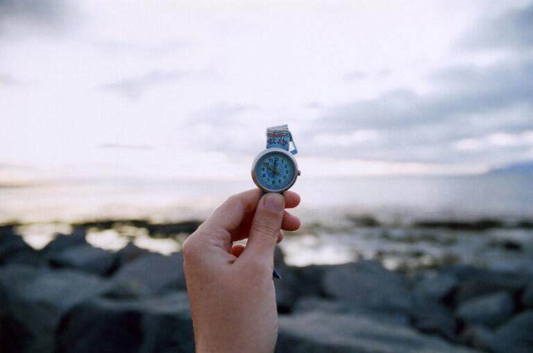 Un mano sujeta un reloj, que marca casi las 12h, mientras se ve el Sol de Medianoche