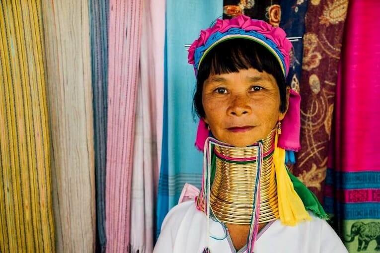 Mujer jirafa en Tailandia con su cuello largo cubierto de anillos dorados.