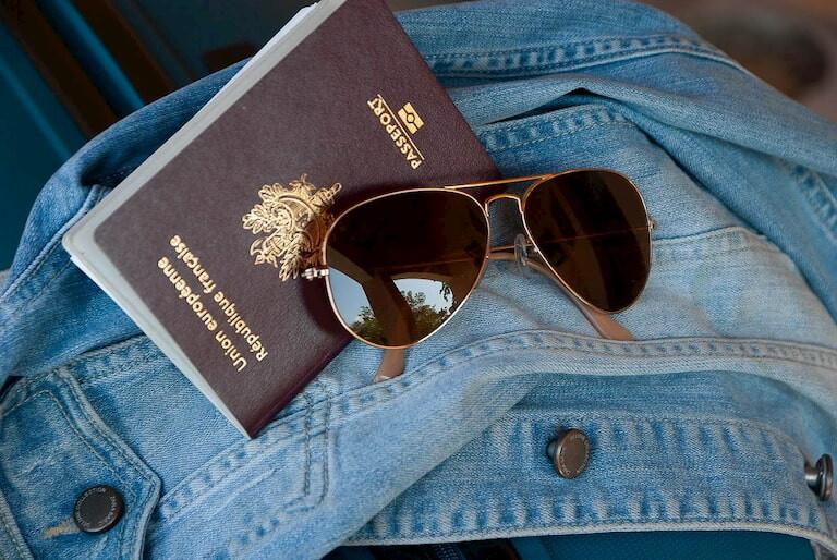 Gafas de sol, pasaporte y chaqueta tejana